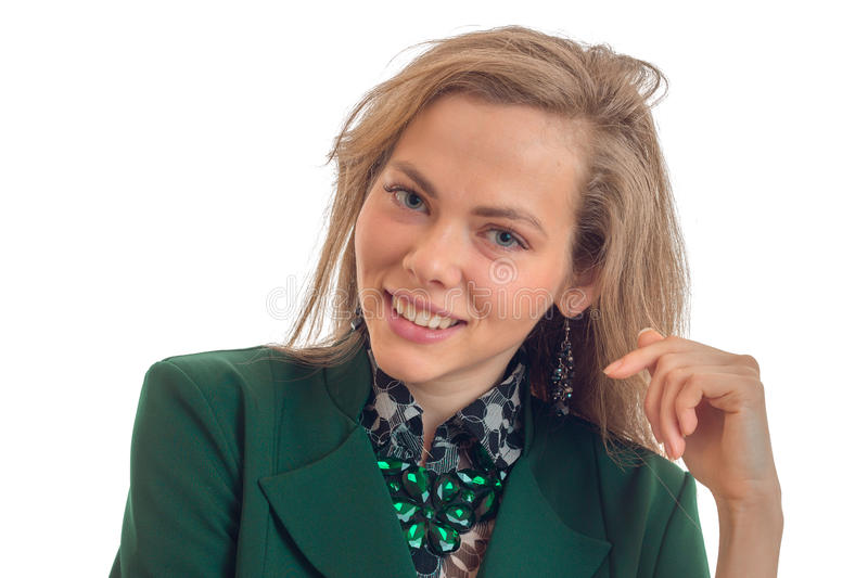 Portrait of a charming young girl in a green jacket that smiles and looks into the camera close-up stock image