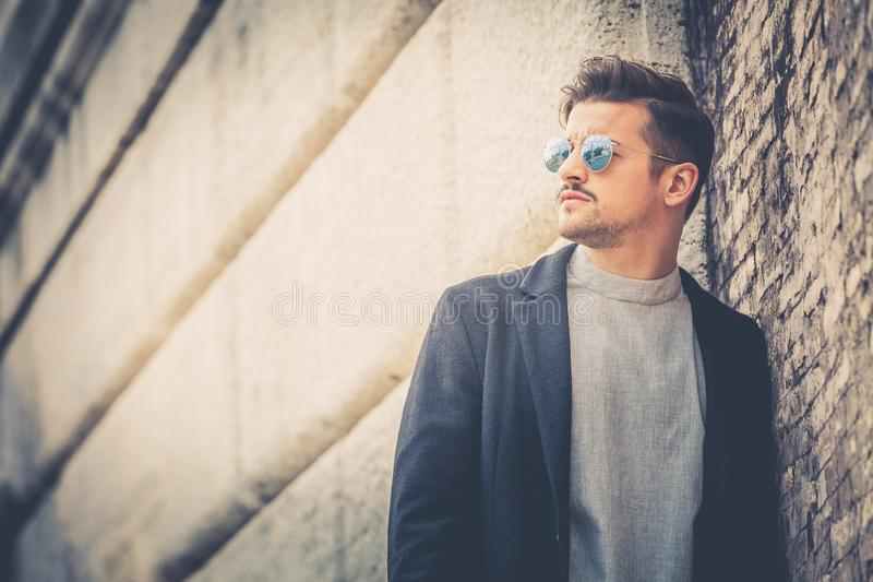 Portrait of charming young man with sunglasses outdoors. Leaning against a brick wall. Trendy masculine hairstyle. Beard and serious and confident look stock image