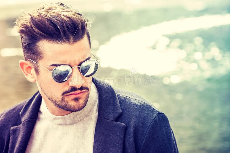 Portrait of charming young man with sunglasses outdoors. Trendy masculine hairstyle. Beard and serious and confident look royalty free stock images