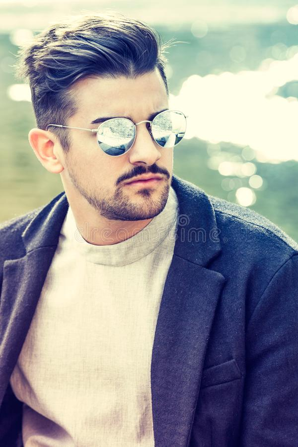 Portrait of charming young man with sunglasses outdoors. Trendy masculine hairstyle. Beard and serious and confident look stock image