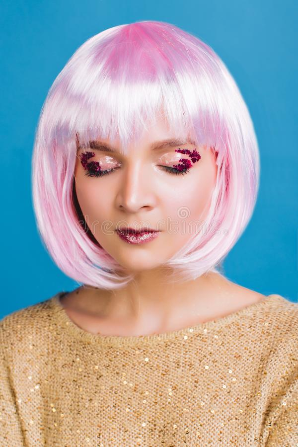 Portrait charming young woman with cut pink hair, closed eyes on blue background. Attractive makeup, pink tinsels on royalty free stock photos