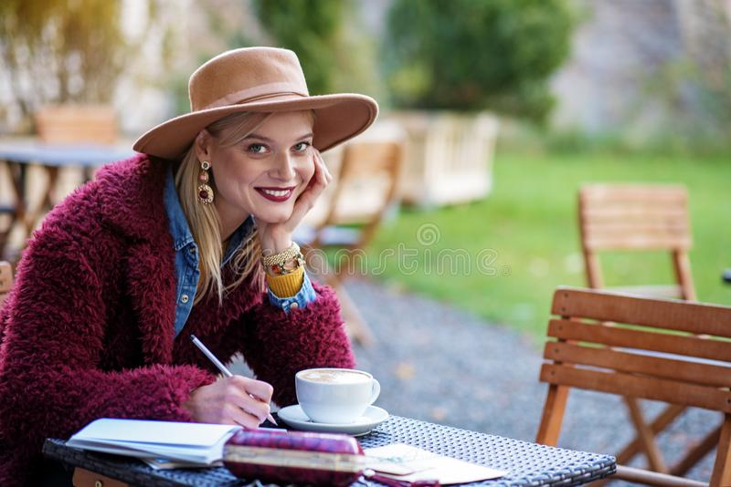 Cute blond lady enjoying free time in cafeteria royalty free stock photo