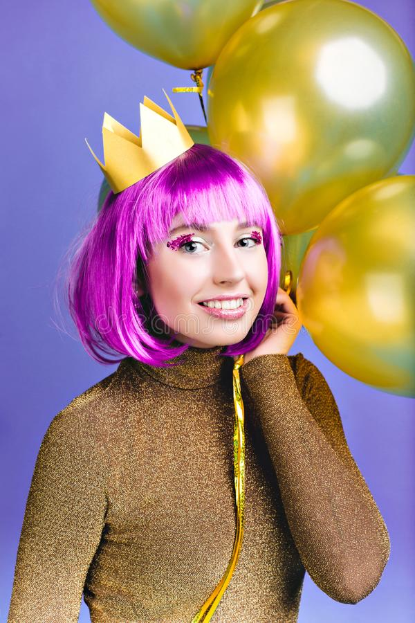 Portrait charming young woman with golden balloons celebrating new year party, carnival on violet background. Cut purple royalty free stock images