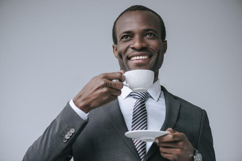 portrait of cheerful african american businessman drinking coffee stock photos