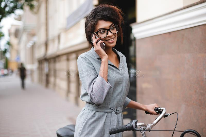 Cheerful African American girl in glasses standing with bicycle and talking on her cellphone. Young beautiful lady with. Portrait of cheerful African American royalty free stock image