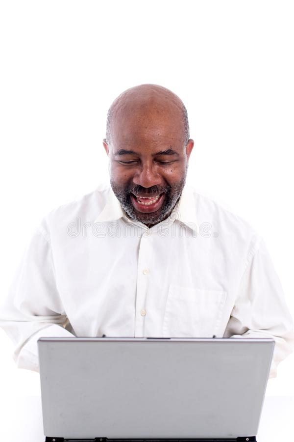 Portrait of cheerful African American software expert laughing while sitting front of a laptop computer royalty free stock images