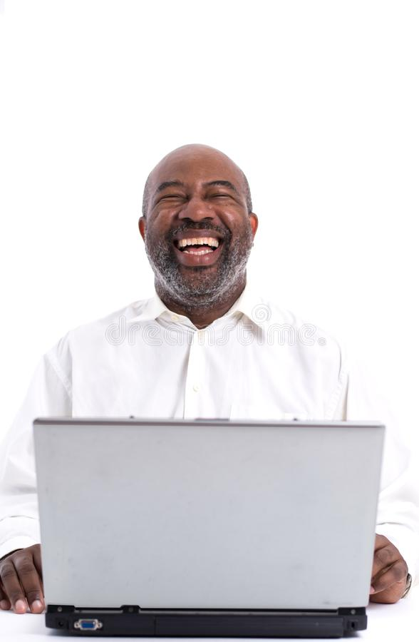 Portrait of cheerful African American software expert laughing while sitting front of a laptop computer stock image