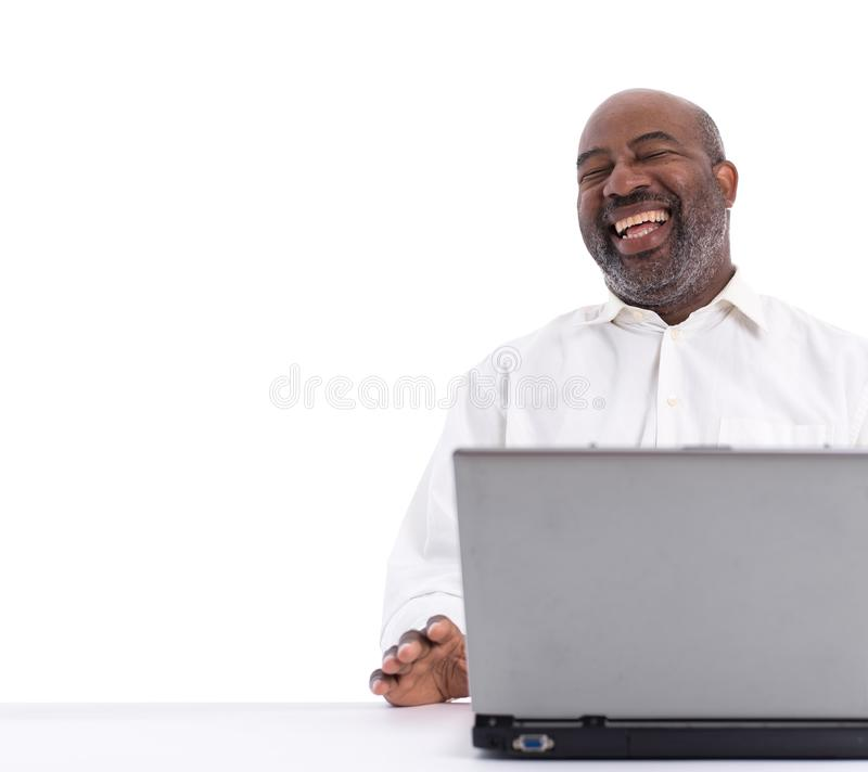Portrait of cheerful African American software expert laughing while sitting front of a laptop computer stock photography