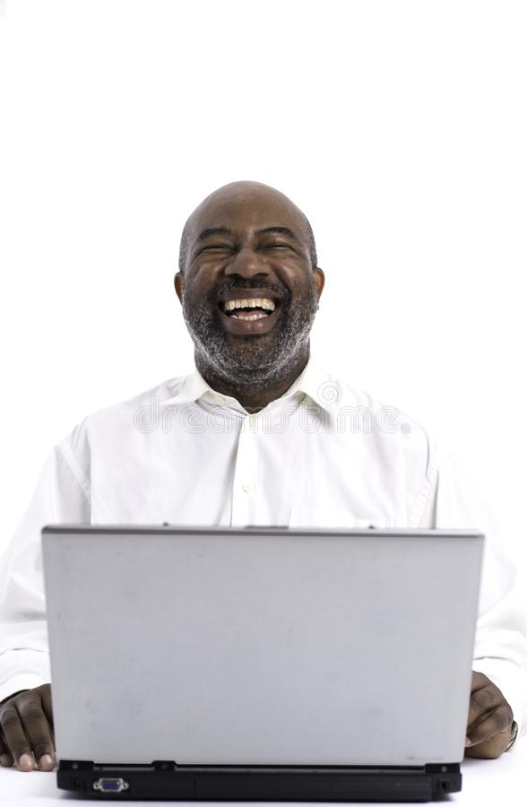 Portrait of cheerful African American software expert laughing while sitting front of a laptop computer stock photos