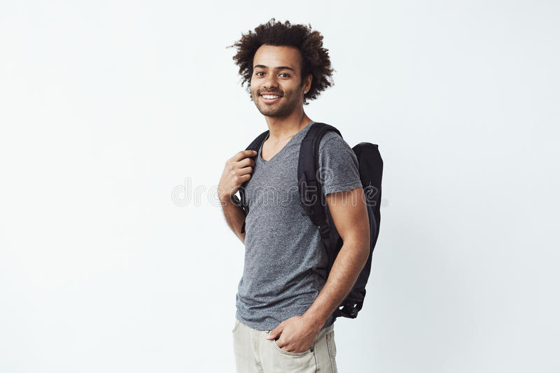 Portrait of cheerful african man with backpack smiling looking at camera ready to go on a long hiking trip or strive for royalty free stock photo