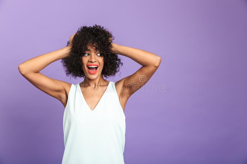 Portrait of a cheerful african woman wearing dress. Standing isolated over violet background, posing royalty free stock photography