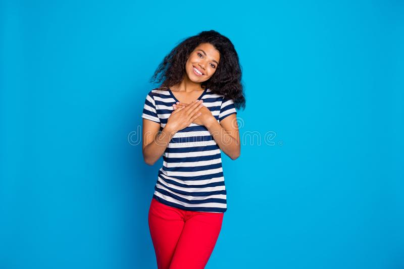 Portrait of cheerful afro american girl put hands palms on chest feel content thankful wear good looking outfit striped royalty free stock photography