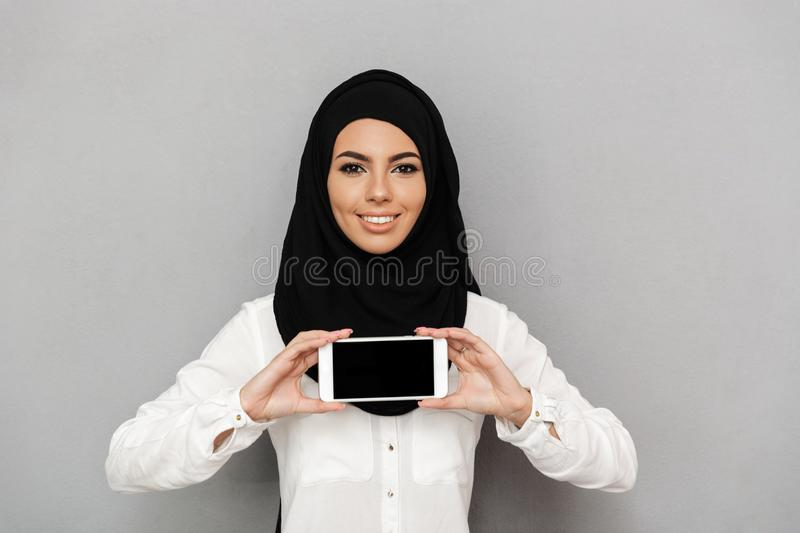 Portrait of cheerful arab prayer woman 20s in religious headscarf with oriental makeup demonstrating black screen of cell phone stock images