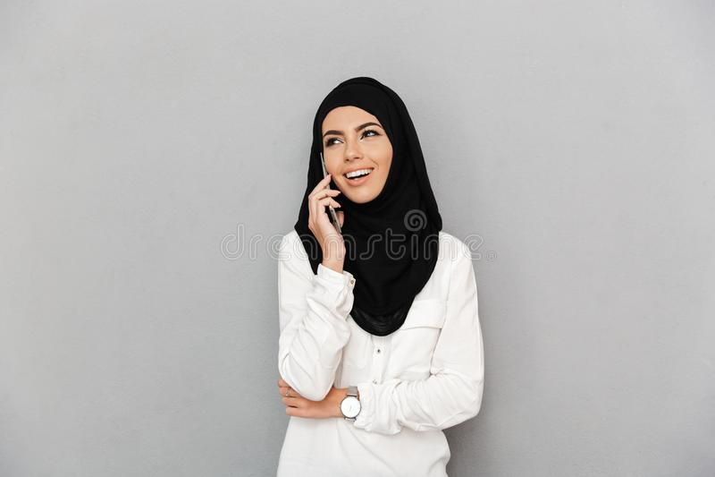 Portrait of cheerful arabic woman in religious headscarf speaking on smart phone, isolated over gray background stock photos