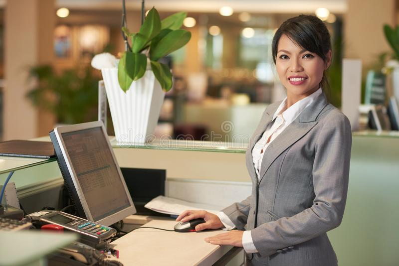 Pretty receptionist. Portrait of cheerful Asain receptionist smiling and looking at camera stock photos