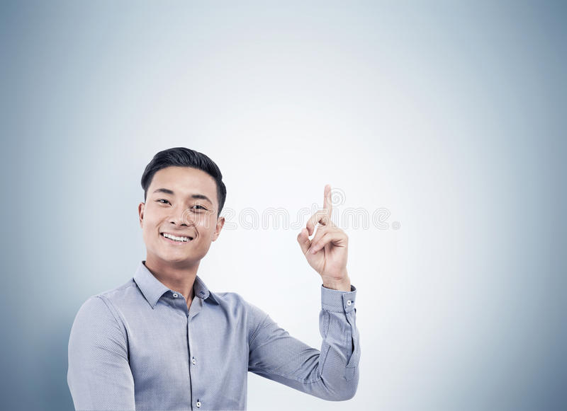 Portrait of cheerful Asian businessman pointing up. Portrait of a smiling young Asian businessman wearing a shirt and pointing upwards while standing near a gray stock photography