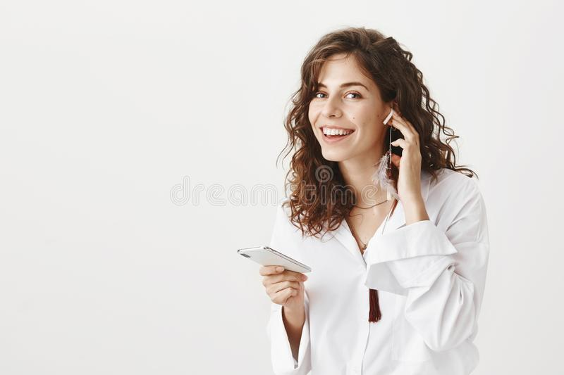 Portrait of cheerful attractive caucasian woman in blouse holding smartphone and wearing wireless earphone, smiling. Broadly and standing against gray stock images