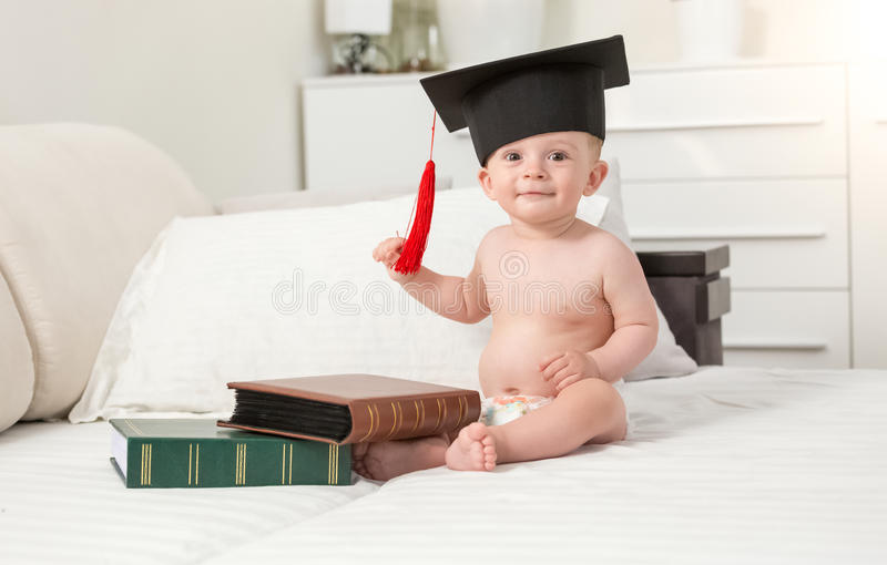 Portrait of cheerful baby boy in black graduating cap seating on royalty free stock image