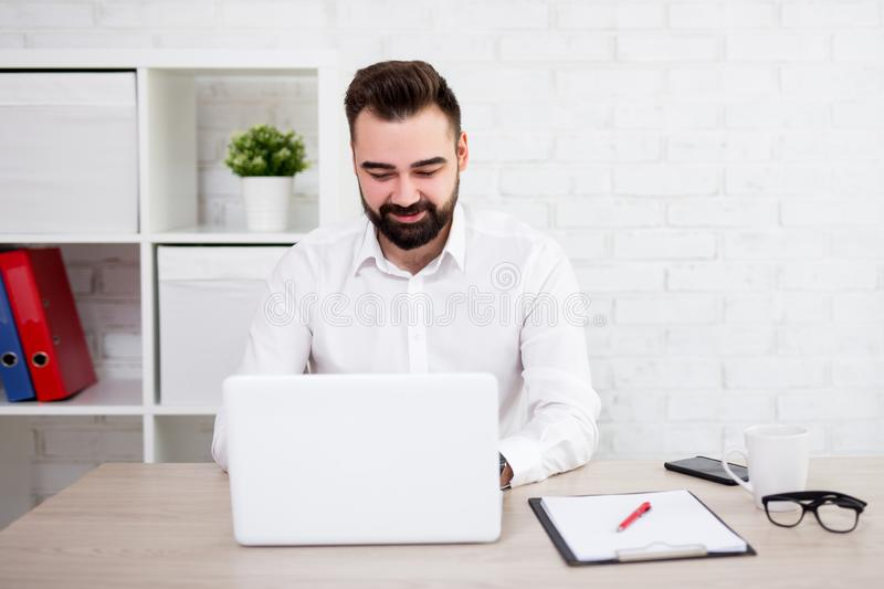 Portrait of cheerful bearded businessman using laptop in office stock photo