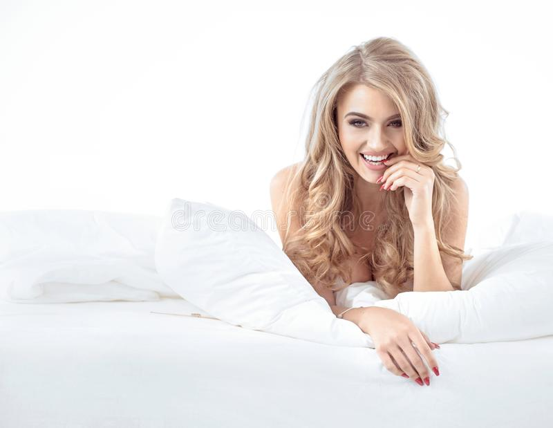 Portrait of a cheerful blonde laying on the soft bed royalty free stock images