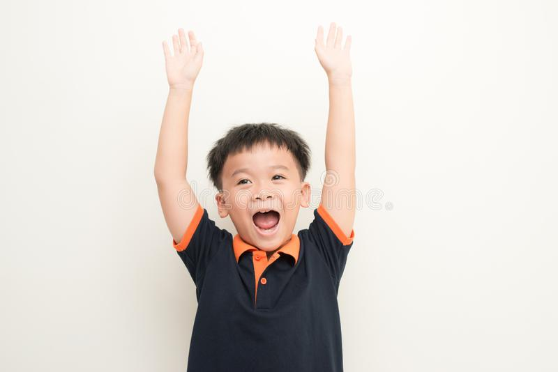 Portrait of cheerful boy with raised hands over isolated white background royalty free stock photo