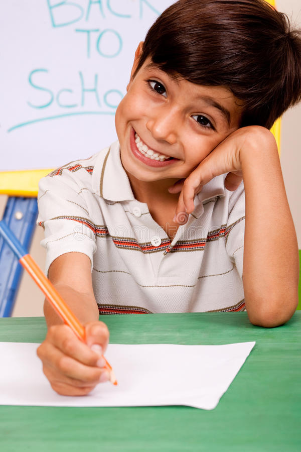 Portrait of cheerful boy writing notes royalty free stock photo