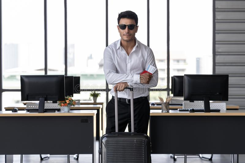 Portrait of cheerful business man holding passport and luggage in workplace of office. Summer vacations concept royalty free stock images
