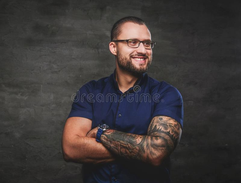Portrait of a cheerful businessman wearing a blue shirt with his arms crossed, isolated on a dark background. Studio stock photo