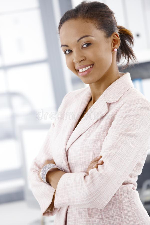 Portrait of cheerful businesswoman. Standing in office with arms crossed stock photography