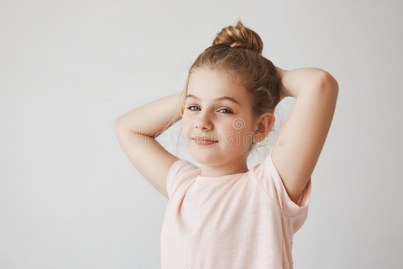 Portrait of cheerful carefree child with blond hair in bun hairstyle smiling brightfully, holding hands behind head stock image