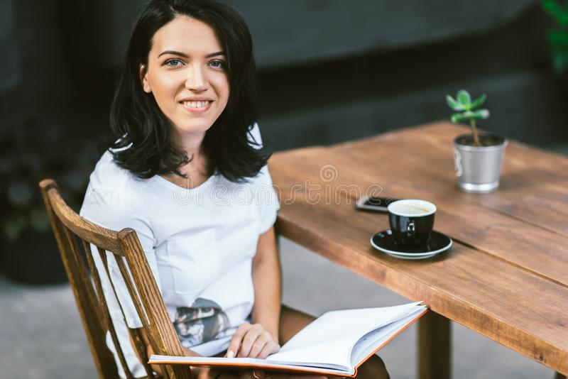 Portrait of cheerful Caucasian smiling woman sitting at terrace cafe, drinking coffee and reading book at break time. People, royalty free stock photos