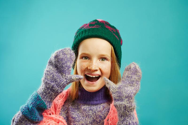 Portrait of cheerful child girl wears winter mittens, warm sweater, hat with pompom and openwork cape scarf on blue stock image