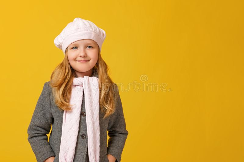 Portrait of a cheerful child in a gray coat and beret on a yellow background. Little girl blonde looks into the camera. stock photos