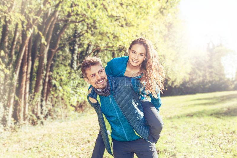 Portrait of a cheerful couple going for a piggyback ride. Happy young caucasian couple in love playing piggyback smiling and having fun in the middle of nature royalty free stock photography