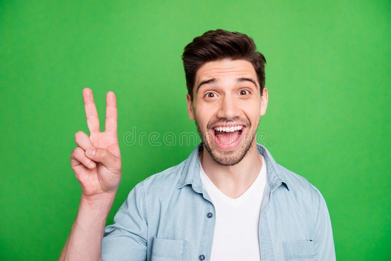 Portrait of cheerful crazy excited overjoyed man having noticed his old acquintance and saying hi to him by showing v. Portrait of cheerful crazy excited stock photography
