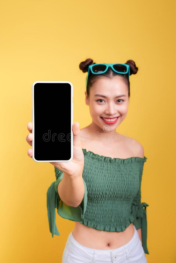 Portrait of a cheerful cute woman showing blank smartphone scree royalty free stock images