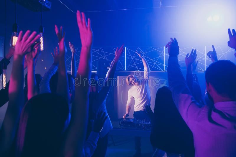 Portrait of cheerful dj party maker raise hands audience moving motion discotheque dancing floor. Portrait of cheerful dj party maker raise hands audience moving royalty free stock photography