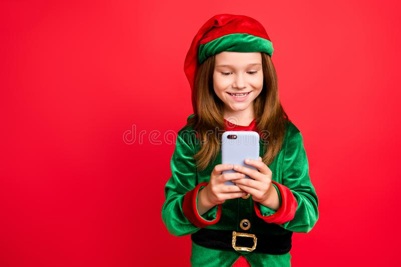 Portrait of cheerful elf in hat with long red head hairstyle use cellphone device read newyear post wearing green royalty free stock images