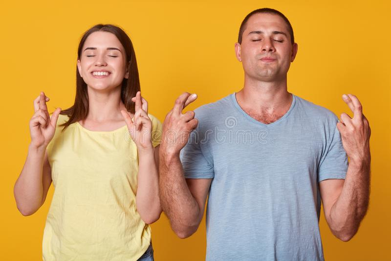 Portrait of cheerful energetic couple standing close to each other, crossing their fingers, raising arms, closing hands, making royalty free stock image