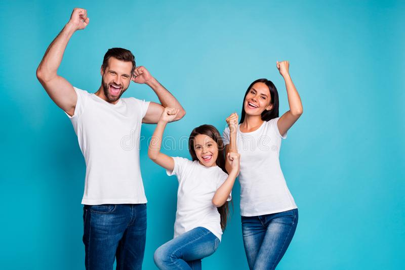 Portrait of cheerful family having brunette hair raising fists screaming yeah celebrating victory wearing white t-shirt stock photography