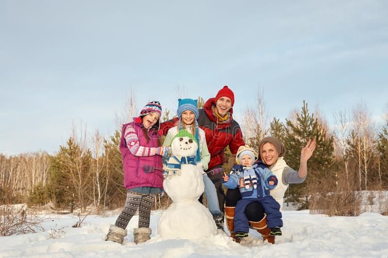 Portrait of a family with snowman. happy children and parents in the winter outdoors stock photos