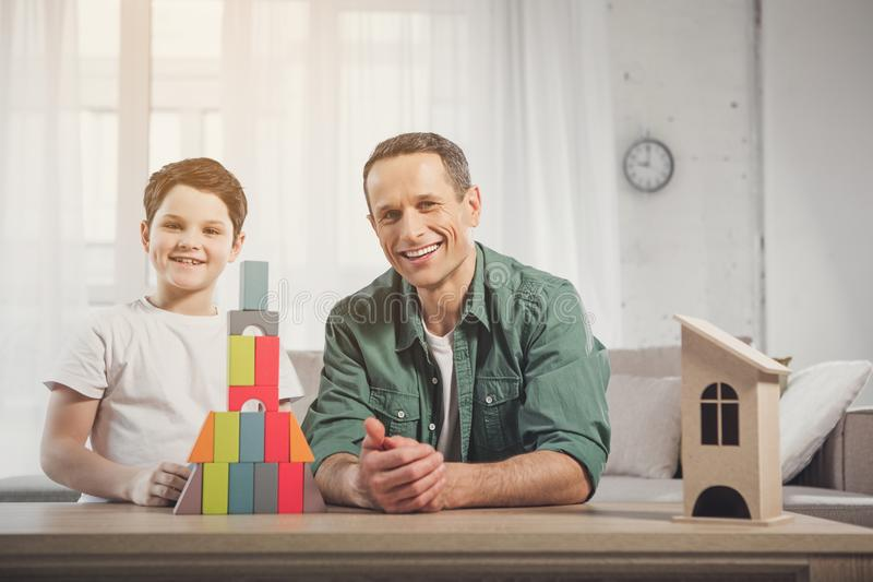 Happy dad and boy playing in living room royalty free stock image