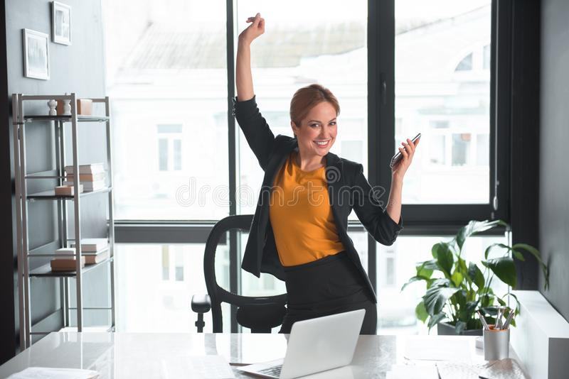 Happy businesswoman rising hands up with phone royalty free stock photography