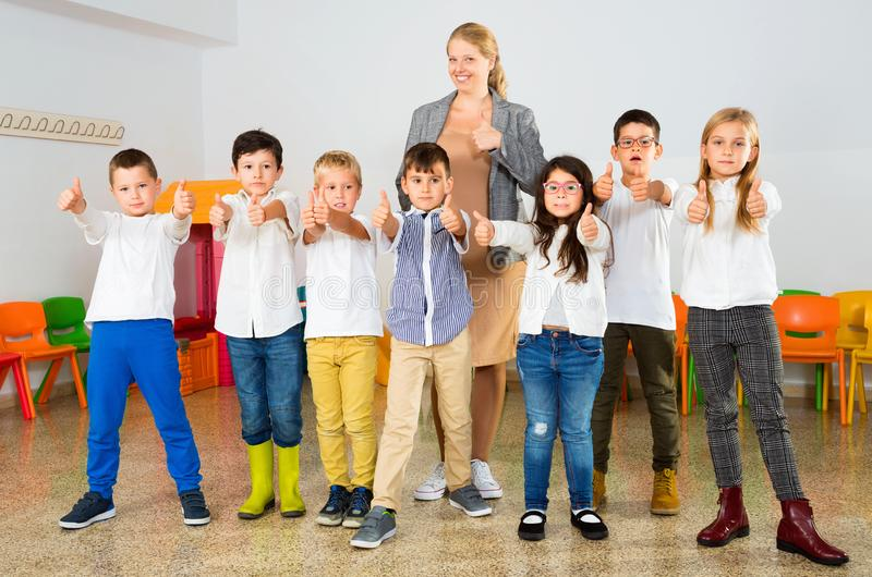 Portrait of cheerful female teacher with her happy schoolkids in classrom stock photography