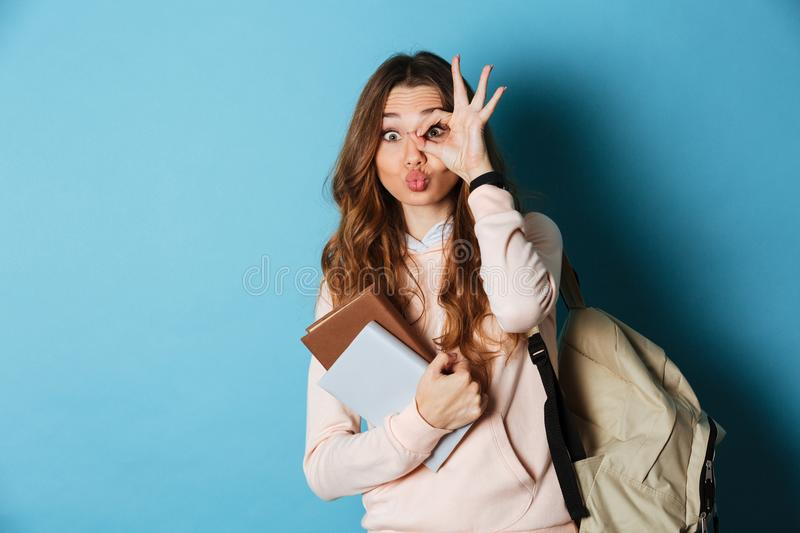 Portrait of a cheerful funny girl student with backpack stock photography