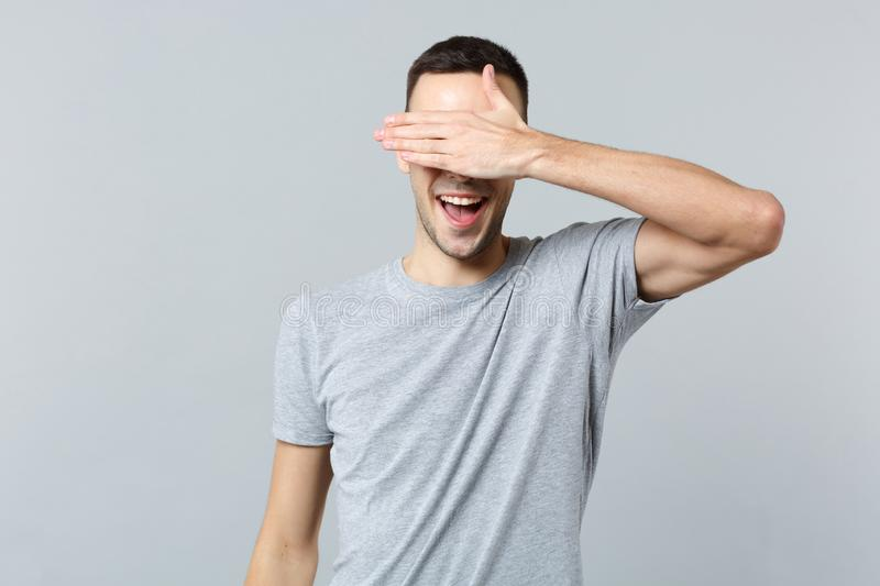 Portrait of cheerful funny young man in casual clothes hiding and covering eyes with hand isolated on grey wall. Background in studio. People sincere emotions stock image