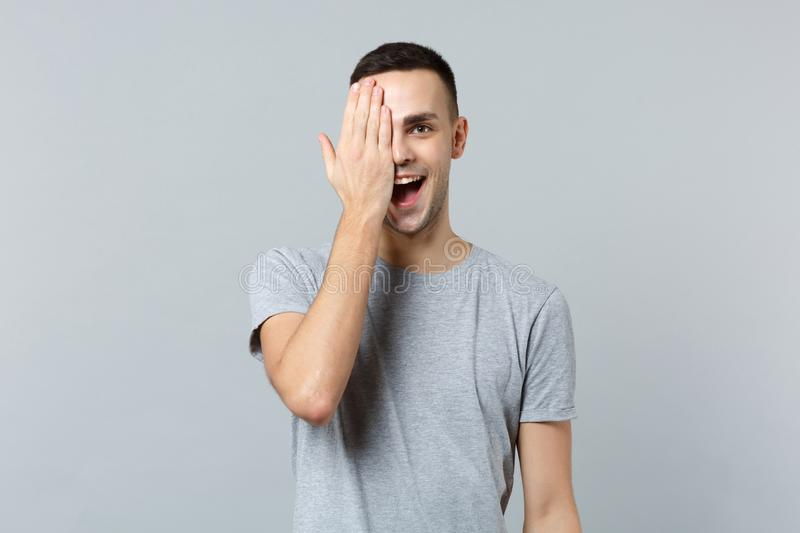 Portrait of cheerful funny young man in casual clothes keeping mouth open covering face with hand isolated on grey. Background in studio. People sincere royalty free stock photos