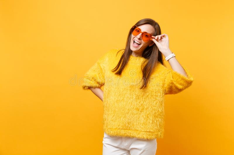 Portrait of cheerful funny young woman in fur sweater, white pants holding heart orange eyeglasses isolated on bright. Yellow background. People sincere stock image