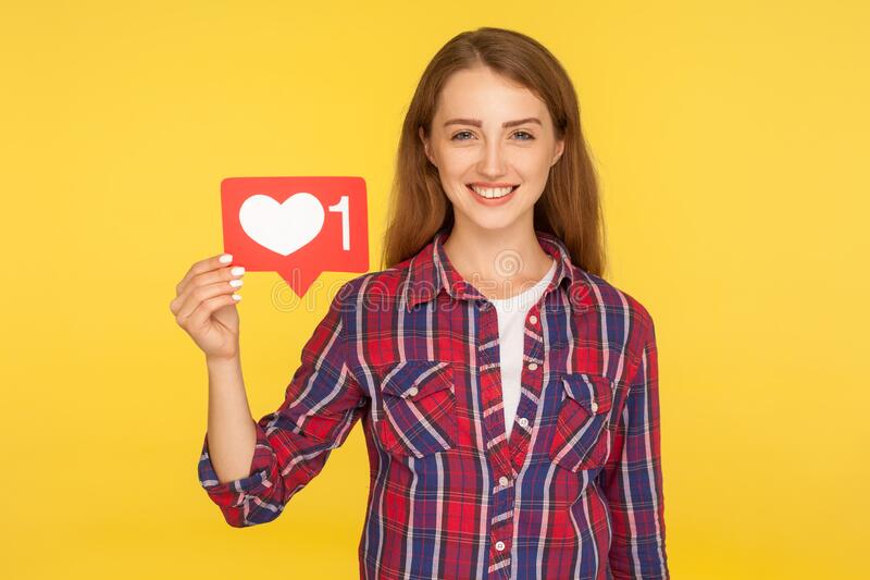 Portrait of cheerful ginger girl in checkered shirt smiling and holding social media like icon, heart button to enjoy content. Subscribe and follow. indoor stock image