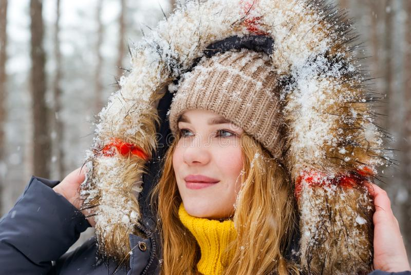 Portrait of cheerful girl in a fur hood in the winter park royalty free stock photo
